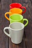 Cuatro tazas de té vacías del color arreglaron en una fila imagen de archivo libre de regalías