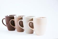 Cuatro tazas grandes en un fondo blanco No aislado, gradación de color, foco selectivo Foto de archivo libre de regalías