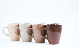 Cuatro tazas grandes en un fondo blanco No aislado, gradación de color, foco selectivo Imagen de archivo
