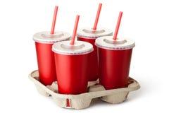 Cuatro tazas para llevar rojas en un soporte de vaso Fotos de archivo