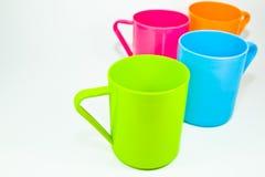 Cuatro tazas plásticas coloridas Fotografía de archivo