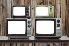 Cuatro televisiones del vintage con las pantallas cortadas y la pared de madera vieja Foto de archivo