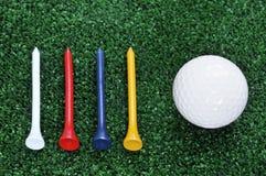 Cuatro tes y pelotas de golf Foto de archivo
