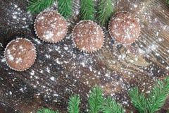 Cuatro tortas de la Navidad, fondo de madera sitiado por la nieve del invierno, Br del abeto Foto de archivo