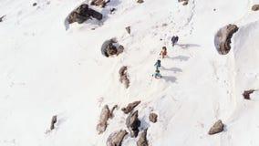 Cuatro turistas suben la montaña, ayudándose con los polos de esquí tiro aéreo con la cámara giratoria del quadcopter metrajes