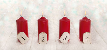 Cuatro velas ardientes rojas del advenimiento en fondo de madera del blanco nevoso Fotos de archivo