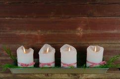 Cuatro velas del advenimiento en una pared roja resistida vieja Fotografía de archivo libre de regalías