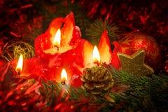 Cuatro velas rojas con la bola y la decoración de la Navidad Fotos de archivo