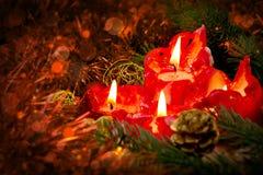 Cuatro velas rojas con la bola y la decoración de la Navidad Fotografía de archivo