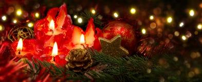 Cuatro velas rojas con la bola y la decoración de la Navidad Foto de archivo libre de regalías