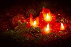 Cuatro velas rojas del advenimiento con la decoración de la Navidad Imagenes de archivo