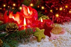 Cuatro velas rojas del advenimiento con la decoración y la nieve de la Navidad Fotografía de archivo libre de regalías