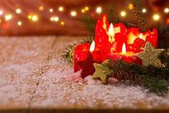 Cuatro velas rojas del advenimiento con la luz de la Navidad Fotos de archivo libres de regalías