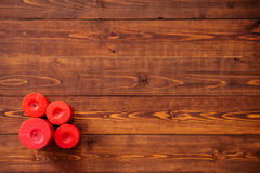 Cuatro velas rojas en la tabla de madera marrón Imágenes de archivo libres de regalías