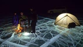 Cuatro viajeros por la derecha del fuego en el hielo en la noche Camping en el hielo La tienda se coloca al lado del fuego La gen almacen de video
