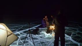 Cuatro viajeros por la derecha del fuego en el hielo en la noche Camping en el hielo La tienda se coloca al lado del fuego La gen metrajes