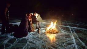 Cuatro viajeros por la derecha del fuego en el hielo en la noche Camping en el hielo La tienda se coloca al lado del fuego La gen almacen de metraje de vídeo