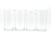 Cuatro vidrios con agua en un vidrio Foto de archivo libre de regalías