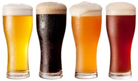 Cuatro vidrios con diversas cervezas. Imagenes de archivo