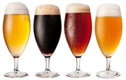 Cuatro vidrios con diversas cervezas. Foto de archivo