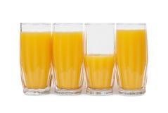 Cuatro vidrios con el zumo de naranja Imagen de archivo libre de regalías