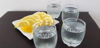 Cuatro vidrios con la vodka en la tabla marrón foto de archivo