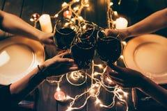 Cuatro vidrios que tintinean de las personas con el vino Foto de archivo