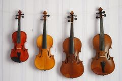 Cuatro violines de diversos tamaños y colores que cuelgan en la pared Imagen de archivo libre de regalías