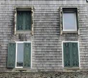 Cuatro Windows con los obturadores decorativos en una casa vieja Imágenes de archivo libres de regalías