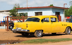 Cuba american yellow vintage car parked on the road Stock Photography