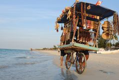 Cuba: Beach souvenier trader pushing his heavy loaded bicycle tr royalty free stock photography