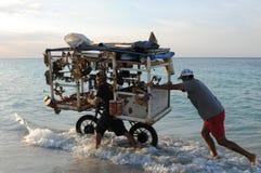 Cuba: Beach souvenier trader at Varadero beach pushing his heavy royalty free stock images