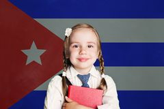 Cuba concept with happy child girl student with book against the flag of Cuban background royalty free stock images