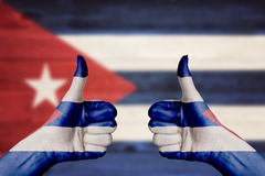 Cuba flag painted on female hands thumbs up Stock Image