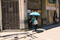 Under umbrella to protect from the sun. Cuba, Havana - 07 April, 2016: a woman is walking at noon with an umbrella to protect herself from the heat of the sun Stock Photo
