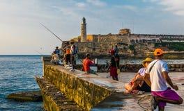 cuba havana Juni 2018 El Malecon av havannacigarren: kubanskt folk som fiskar på solnedgången arkivbilder