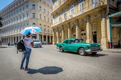Cuba, Havana - Mar 9th 2018 - Lonely woman waiting for a transport while a old green car pass by her, dressing a Cuba t-shirt in a royalty free stock photos