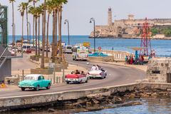 CUBA, HAVANA - MAY 5, 2017: American colorful retro cars traveling along the waterfront. Copy space for text. Royalty Free Stock Photos