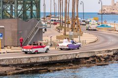CUBA, HAVANA - MAY 5, 2017: American colorful retro cars traveling along the waterfront. �opy space for text. Royalty Free Stock Photos