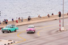 CUBA, HAVANA - MAY 5, 2017: American pink retro car rides along the Malecon waterfront. Copy space for text. CUBA, HAVANA - MAY 5, 2017: American pink retro car Royalty Free Stock Photo
