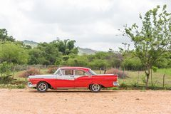 CUBA, HAVANA - MAY 5, 2017: American red retro car in the countryside. Copy space for text. Stock Photos
