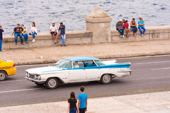 CUBA, HAVANA - MAY 5, 2017: American retro car rides along the Malecon waterfront. Copy space for text. CUBA, HAVANA - MAY 5, 2017: American retro car rides Stock Photos