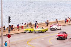 CUBA, HAVANA - MAY 5, 2017: American retro cars drive along the Malecon waterfront. Copy space for text. CUBA, HAVANA - MAY 5, 2017: American retro cars drive Stock Images