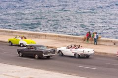 CUBA, HAVANA - MAY 5, 2017: American retro cars drive along the Malecon waterfront. Copy space for text. CUBA, HAVANA - MAY 5, 2017: American retro cars drive Royalty Free Stock Photography