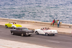 CUBA, HAVANA - MAY 5, 2017: American retro cars drive along the Malecon waterfront. Copy space for text. CUBA, HAVANA - MAY 5, 2017: American retro cars drive Stock Photo