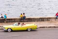 CUBA, HAVANA - MAY 5, 2017: American yellow retro cabriolet rides along the Malecon seafront. Copy space for text. Royalty Free Stock Image