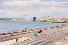 CUBA, HAVANA - MAY 5, 2017: Cars drive along the Malecon waterfront. Copy space for text. CUBA, HAVANA - MAY 5, 2017: Cars drive along the Malecon waterfront Royalty Free Stock Photo
