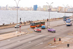 CUBA, HAVANA - MAY 5, 2017: Cmerican retro cars drive along the Malecon waterfront. Copy space for text. CUBA, HAVANA - MAY 5, 2017: Cmerican retro cars drive Stock Image