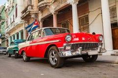Cuba, Havana: O carro clássico americano com bandeira de Cuba estacionou no Fotografia de Stock