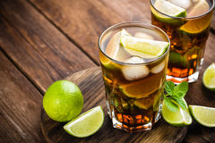 Cuba Libre cocktail with cola, lime and ice in glass, cold longdrink. On wooden background stock photo